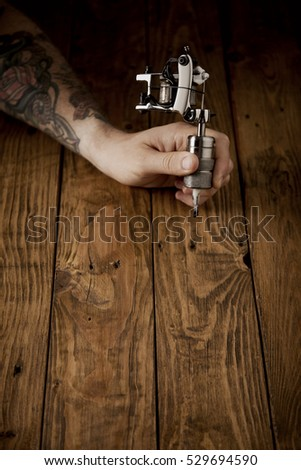 Brutal master's hand with a custom made chrome plated tattoo machine for countouring above rustic wooden table, vertical image, top view
