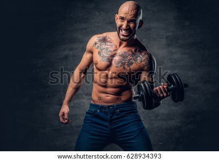 Brutal shirtless shaved head, muscular male with tattoos on his chest and arms holds dumbbell.