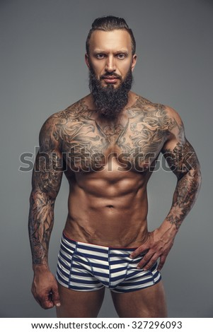 Brutal tattooed man in stripes panties posing over grey background.