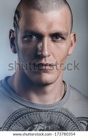 Brutal, tattooed man portrait - stock photo