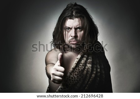 Brutal wild man shows thumb up. - stock photo