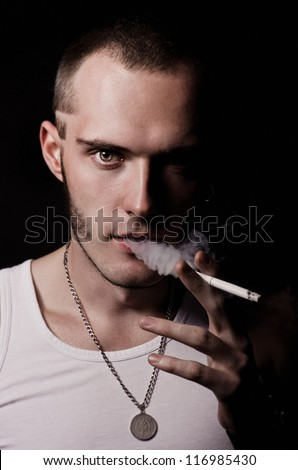 Brutal young guy smoking a cigarette