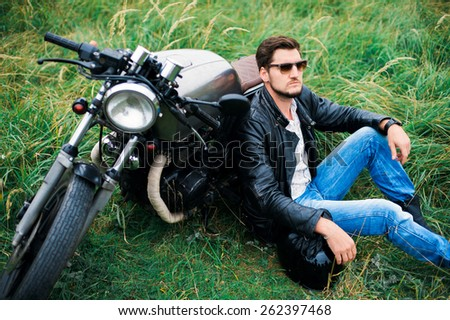 Brutal young man in sunglasses, blue jeans and a black leather jacket sitting near a motorcycle on the field with a helmet - stock photo