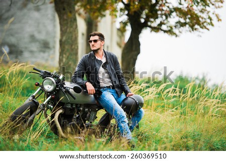 Brutal young man in sunglasses sitting around a motorcycle on the street - stock photo