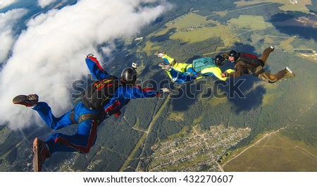 BRYANSK/RUSSIA - AUGUST 2, 2015:  Flying operator with a camera on his helmet  shoots a group of two skydivers in the air