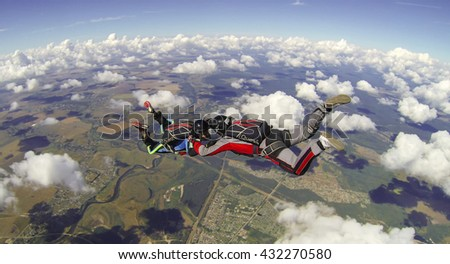 BRYANSK/RUSSIA - AUGUST 16, 2014:  Two holding skydivers in the cloudy sky