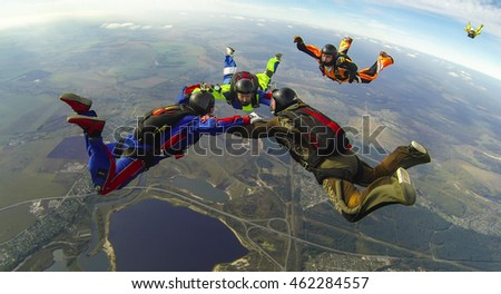 "BRYANSK/RUSSIA - OCTOBER 4,, 2015:  A group of three skydivers make a ""ring"" formation in the air and two more skydivers try to join them"