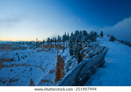 Bryce canyon panorama with snow and fog in Winter with red rocks  - stock photo