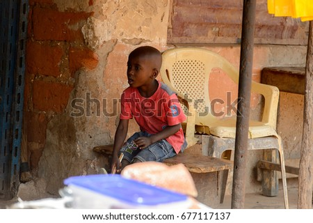 BUBAQUE, GUINEA BISSAU - MAY 5, 2017: Unidentified local little boy in red shirt sits in a village of the Bubaque island. People in G.-Bissau still suffer of poverty