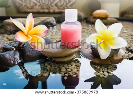 Bubble bath and shower gel decorated in zen style with pebble rock and flower with relaxing mood - stock photo