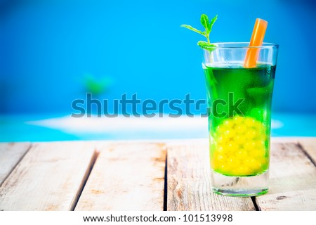 Bubble tea at the beach. Standing on a wooden deck near the strand with copyspace. - stock photo