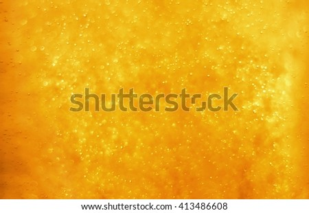 Bubbles floating in the liquid orange drink, abstract image. - stock photo