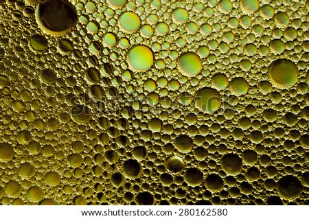Bubbles oil and water on yellow background - stock photo