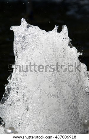 Bubbling streams of water in a fountain with foam close up