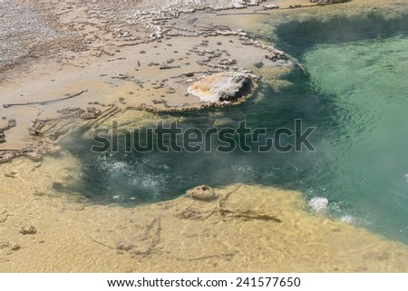 Bubbling Water in a Colorful Hot Spring in the Norris Geyser Basin in Yellowstone - stock photo