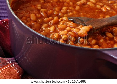 Bubbly hot baked beans (brown sugar recipe) right out of the oven.  Closeup with shallow dof. - stock photo
