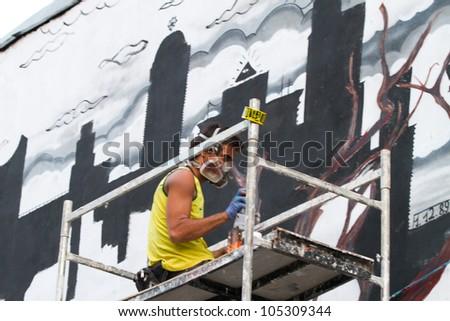 BUCHAREST - JUNE 15: Unknown artist painting graffiti on Arthur Verona - Painter street  done as part of the Street Delivery 2012, on June 15, 2012 in Bucharest, Romania - stock photo