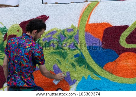 BUCHAREST - JUNE 15: Unknown artists paint graffiti on Arthur Verona - Painter street, as part of the Street Delivery 2012, on June 15, 2012 in Bucharest, Romania - stock photo