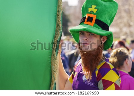 BUCHAREST - MARCH 16: Unidentified young man wearing traditional Irish green hat holds large green flag during the 2nd St. Patrick's Day Parade on March 16, 2014 in Bucharest, Romania. - stock photo
