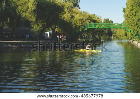 Bucharest, ROMANIA - August 14 2016: Man rowing on his boat and people strolling through IOR park. BUCHAREST -August 14 2016