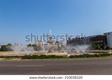 Bucharest, Romania - August 10, 2014: The water fountains in Unirii Square cool down the atmosphere on a hot summer's day on 10th of August 2014 in Bucharest Romania. - stock photo