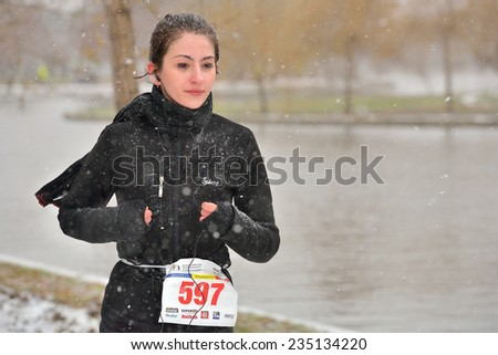 BUCHAREST, ROMANIA - DECEMBER 1st: Cute unidentified marathon runner competes while snowing, at the National Day of Romania Marathon 2014, December 1st, 2014 in Bucharest, Romania  - stock photo