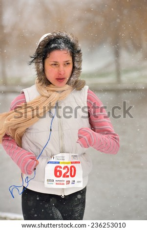 BUCHAREST, ROMANIA - DECEMBER 1st: unidentified marathon girl runner competes while snowing, at the National Day of Romania Marathon 2014, December 1st, 2014 in Bucharest, Romania