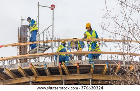 Bucharest, Romania - February 05, 2016: Workers welding metal bars in a construction yard on rooftop of a new building