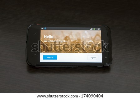"BUCHAREST, ROMANIA - JAN 28,2014:Photo of a HTC Desire device,showing the Twitter.com homepage of the Android app featuring the image of a crowd of hands with the message ""Hello. Welcome to Twitter"". - stock photo"