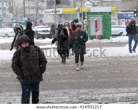 Bucharest, Romania, 4 January 2016. People are seen crossing the street during a blizzard.