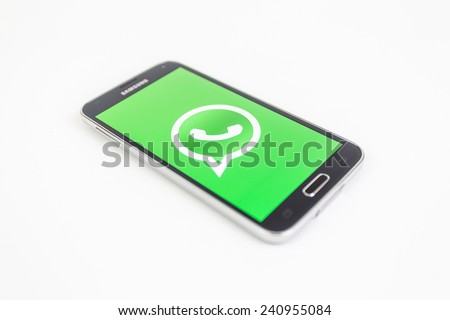 Bucharest, Romania - January 1st, 2015: Brand new black Samsung Galaxy S5 on white background. WhatsApp is an instant messaging app for smartphones that operates under a subscription business model. - stock photo