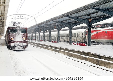 BUCHAREST, ROMANIA - JANUARY 17, 2016: Train of the National Railway Company (CFR) who arrived during a snow storm in the largest railway station in Romania - Gara de Nord