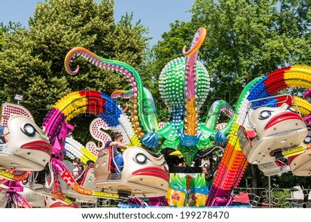 BUCHAREST, ROMANIA - JUNE 08, 2014: Children Having Fun In Octopus Ride In Amusement Park (Tineretului Park) On Summer Day. Created in 1965 is one of the largest fun parks in south Bucharest. - stock photo