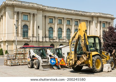 BUCHAREST, ROMANIA - JUNE 09, 2014: Construction Vehicles Restyle Victory Street (Calea Victoriei) Of Bucharest. From 1692 Calea Victoriei (Victory Avenue) is a major avenue in central Bucharest. - stock photo