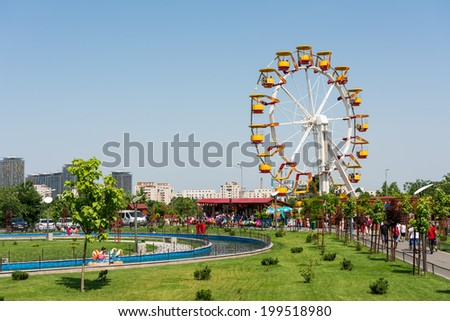 BUCHAREST, ROMANIA - JUNE 08, 2014: Giant Ferris Wheel In Youths Public Amusement Park (Tineretului Park) On Summer Day. Created in 1965 is one of the largest fun parks in south Bucharest. - stock photo