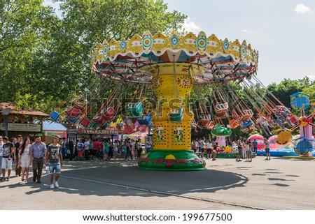 BUCHAREST, ROMANIA - JUNE 08, 2014: People Riding Ferris Wheel In Youths Public Amusement Park (Tineretului Park) On Summer Day. - stock photo