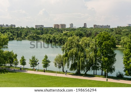 BUCHAREST, ROMANIA - JUNE 08, 2014: People Walking In Youths Public Park (Tineretului Park) On Summer Day. The park was created in 1965 and is one of the largest parks in south Bucharest.