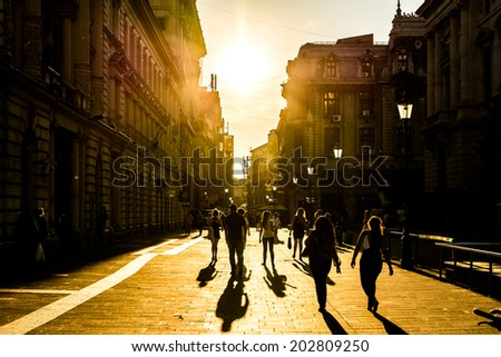 BUCHAREST, ROMANIA - JUNE 30, 2014: Tourists Visiting Downtown Lipscani Street At Sunset. Lipscani is one of the most busiest streets of Bucharest. - stock photo