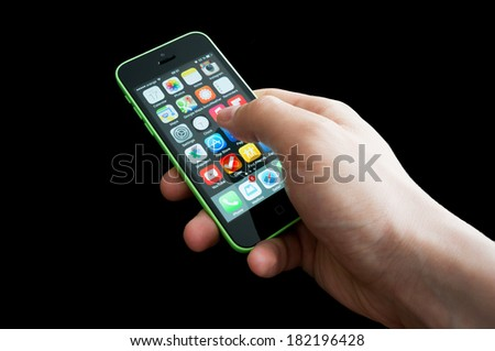 BUCHAREST, ROMANIA - MARCH 17, 2014: Photo an iphone 5C home screen full of icons with the user's hand - stock photo
