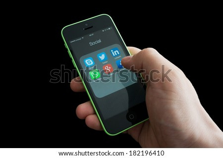 BUCHAREST, ROMANIA - MARCH 17, 2014: Photo of hand of a user of social media apps on an iphone screen