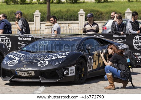 BUCHAREST, ROMANIA - MAY 7: Photographer taking pictures and Lamborghini in background on May 7, 2016 in Bucharest. The car is part of the Gumball 3000 Dublin to Bucharest Charity Grid Rally. - stock photo