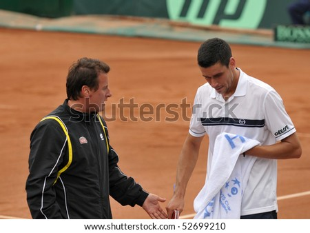 BUCHAREST, ROMANIA - MAY 9:  Romania's captain Andrei Pavel is advising Victor Hanescu during the fourth match of the Davis Cup meeting between Romania and Ukraine at the BNR Arenas on May 9, 2010 in Bucharest, Romania. - stock photo