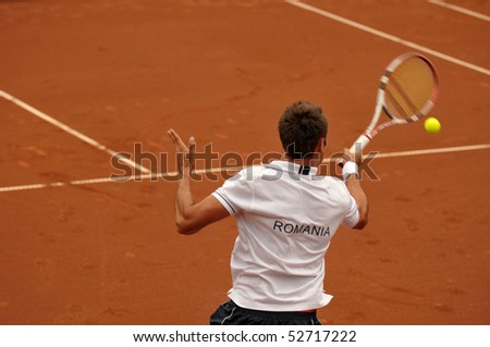 BUCHAREST, ROMANIA - MAY 9: Romania's Marius Copil plays during the fifth match of the Davis Cup meeting between Romania and Ukraine at the BNR Arenas on May 9, 2010 in Bucharest, Romania. - stock photo