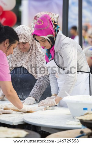 BUCHAREST, ROMANIA - MAY 17: Turkish women knead the dough for traditional suberek pie during the celebratory event Turkish Festival on May 17, 2013 in Bucharest, Romania.