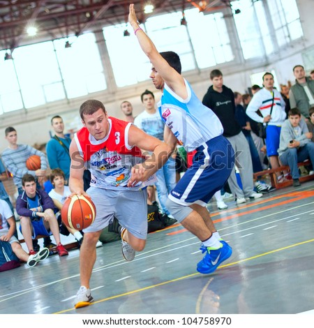 BUCHAREST, ROMANIA - MAY 20: Unknown bascketball  players perform during the game Sport Arena Streetball 3x3, Play On (red) vs. Tiki Taka Polit (blue) on May 20, 2012 in Bucharest, Romania - stock photo