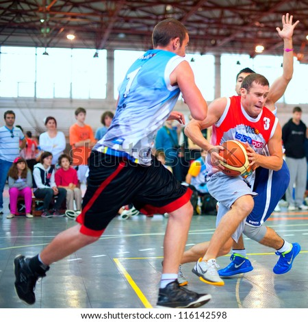 BUCHAREST, ROMANIA - MAY 20: Unknown basketball players perform during the game Sport Arena Streetball 3x3, Play On (red) vs. Tiki Taka Polit (blue) on May 20, 2012 in Bucharest, Romania - stock photo
