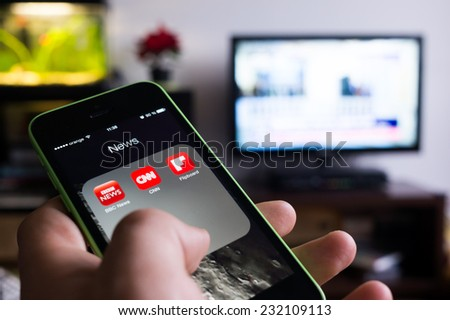 BUCHAREST, ROMANIA - NOVEMBER 21, 2014: Photo of hand holding an iphone with news apps on screen and tv set in the background with news channel