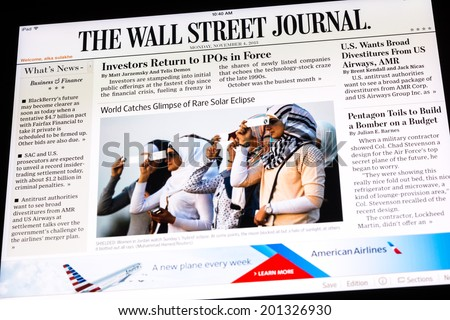 BUCHAREST, ROMANIA - NOVEMBER 04, 2013: The Wall Street Journal Newspaper On Apple iPad Tablet. Is an American international daily newspaper with a special emphasis on business and economic news. - stock photo
