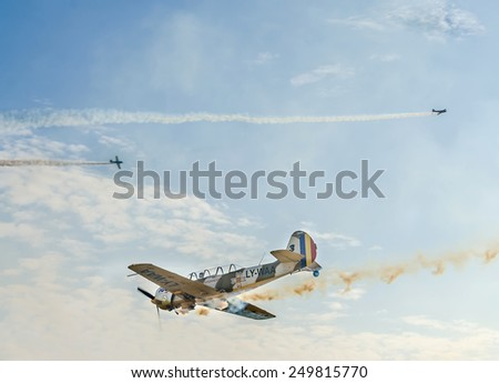 BUCHAREST, ROMANIA - OCTOBER 4, 2014. Aerobatic airplane pilots training in the sky of the city. Colored airplanes with trace smoke