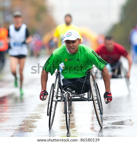BUCHAREST, ROMANIA - OCTOBER 8: An unidentified wheel chair competitor participates with marathon runners at Bucharest International Marathon 2011, October 8, 2011 in Bucharest, Romania - stock photo